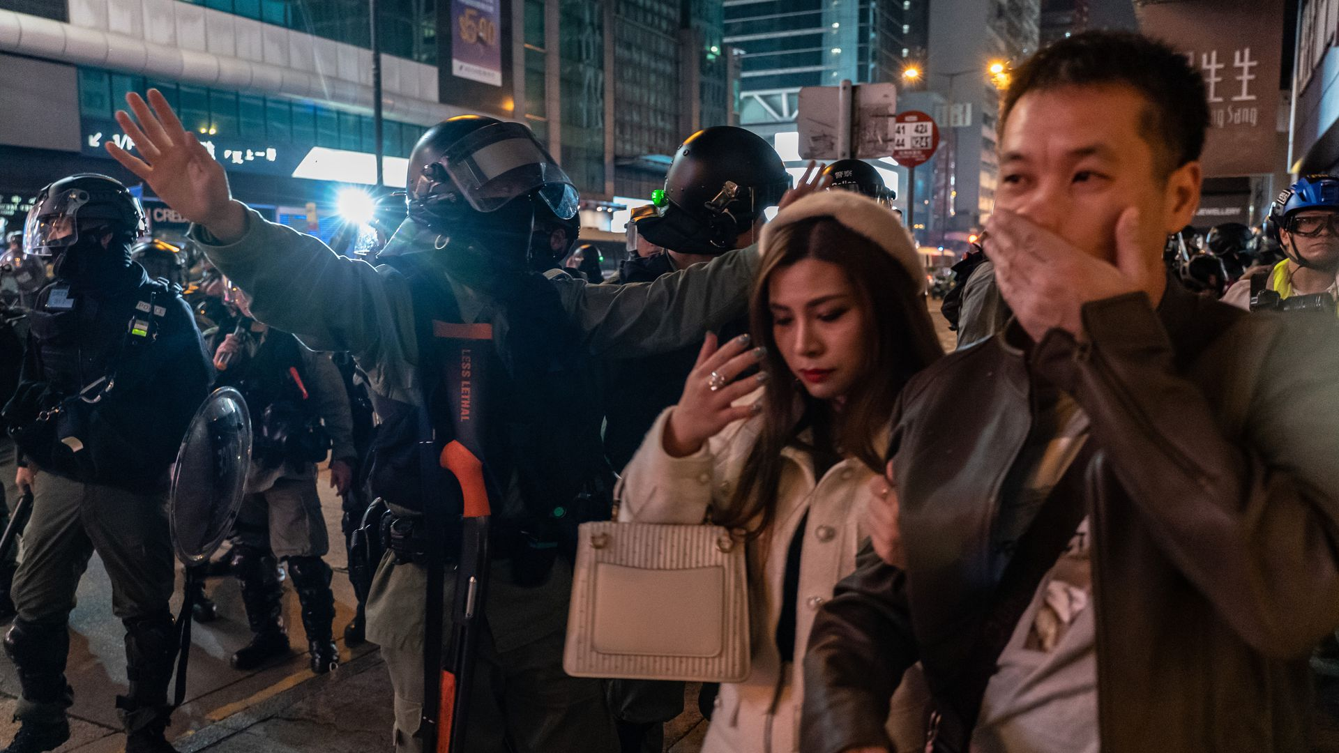 Riot police motion pedestrians away on a street during Christmas night in Mongkok district on December 25, 2019 in Hong Kong, China.