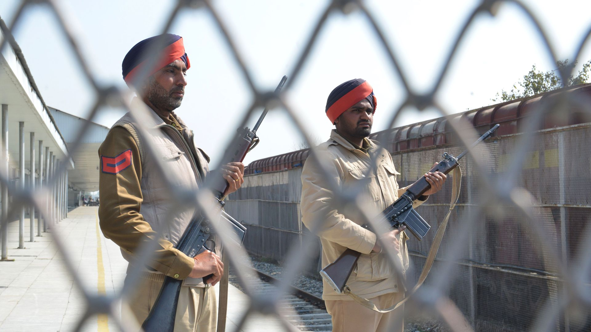 In this image, Indian Punjab Police stand guard with assault weapons behind a gated fence at a train station.