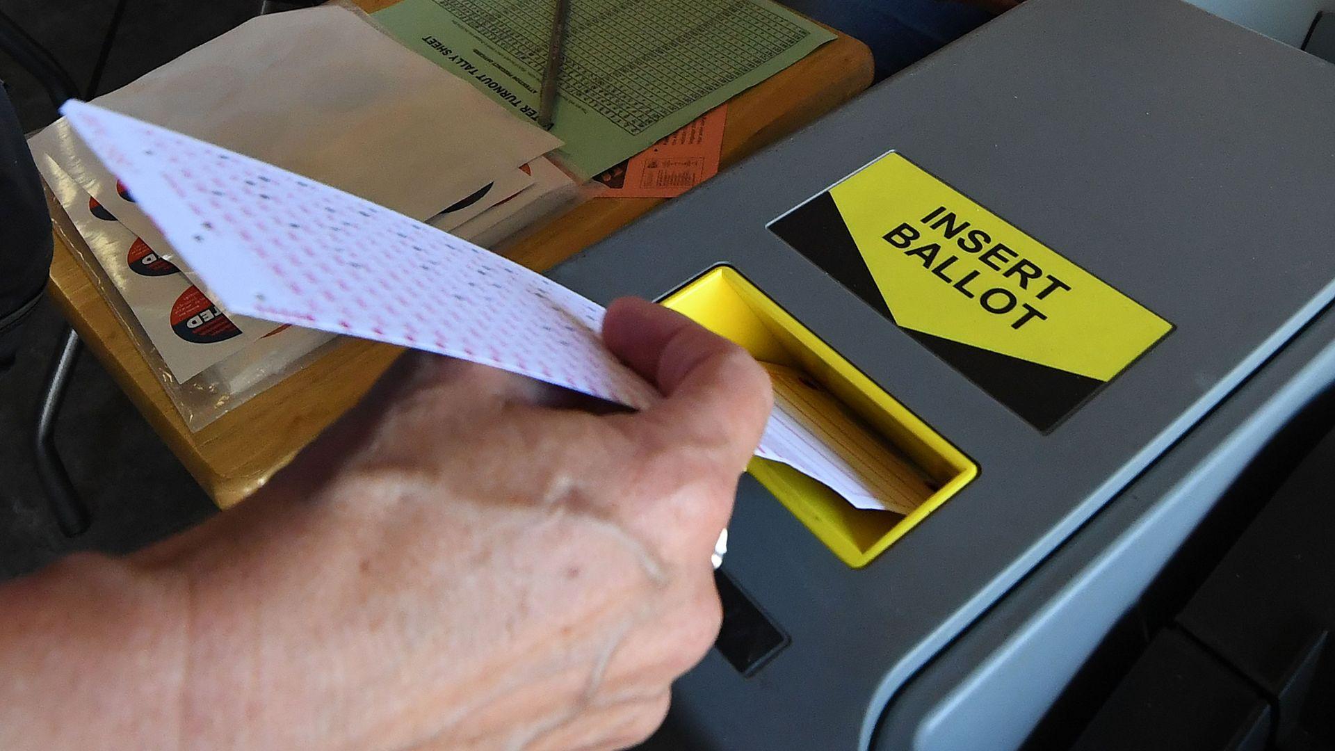 A woman puts a ballot into a scanning machine