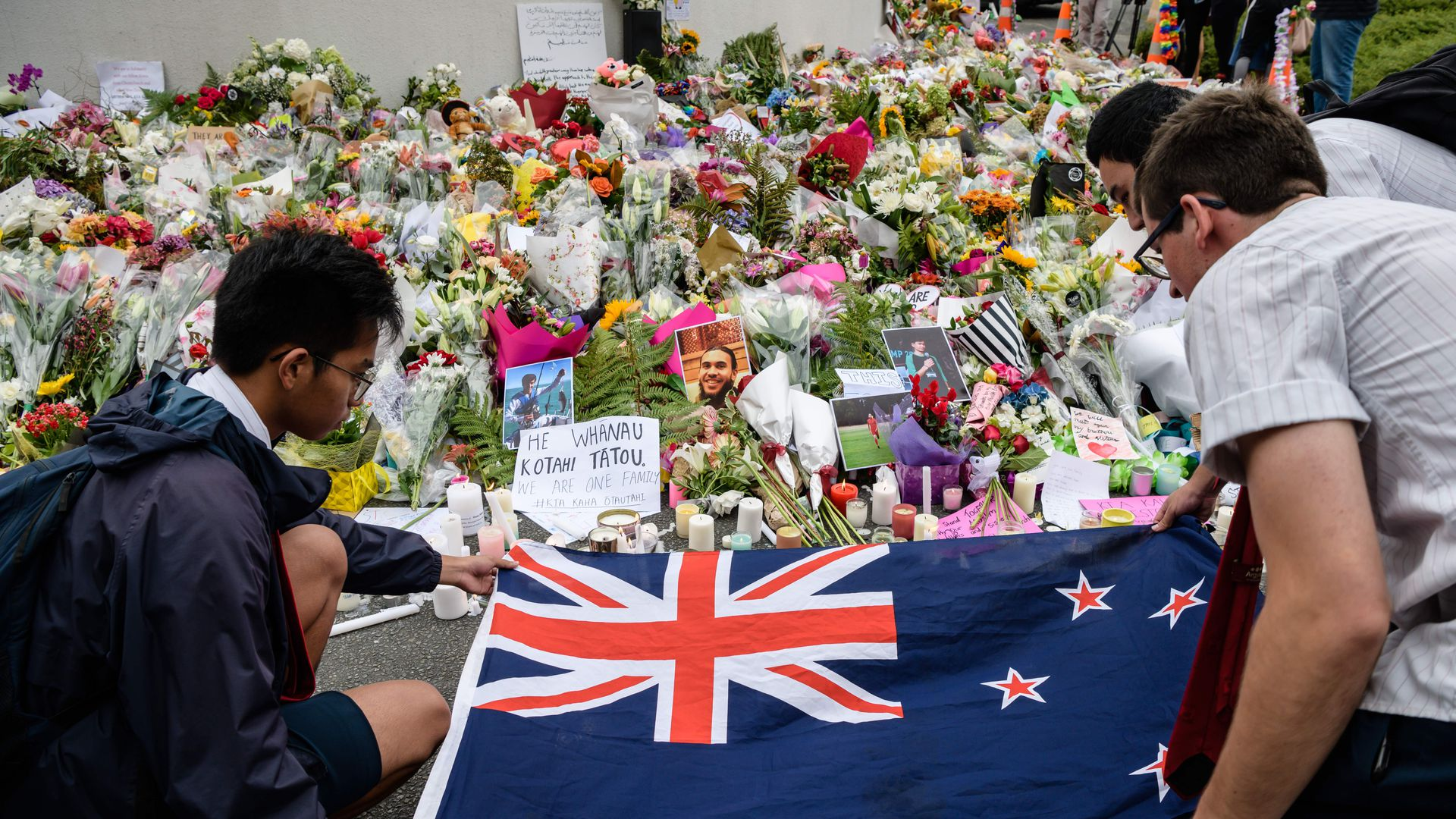 Students display the New Zealand national flag next to flowers during a vigil in Christchurch on March 18, 2019.