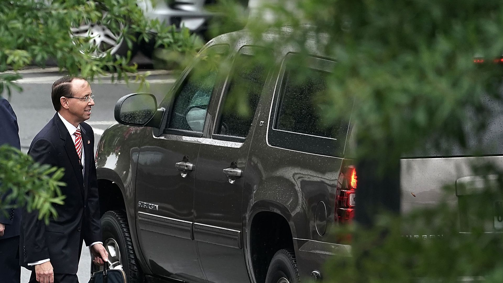 Rod Rosenstein walking near a car, with a tree shrouding the picture