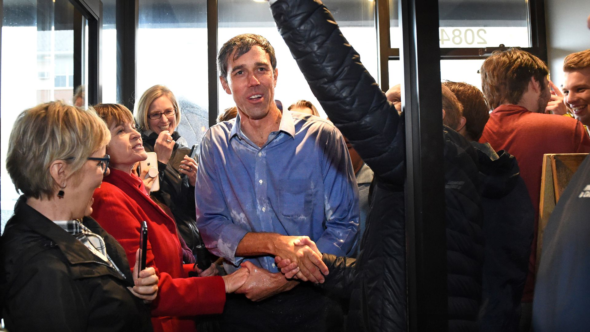 In this image, Beto stands soaked in rain and shaking multiple hands while walking through a door.