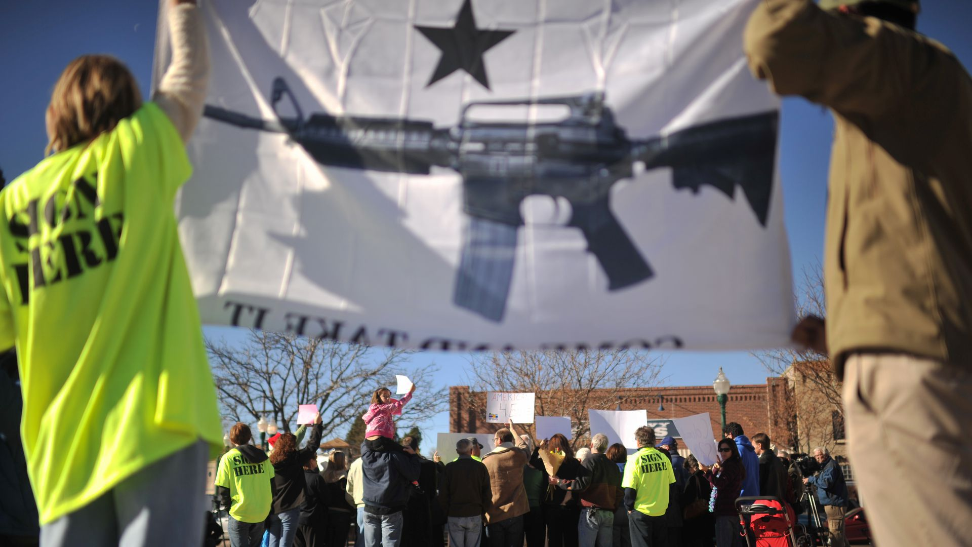 Pro-gun rights protesters hold up a flag with a gun on it