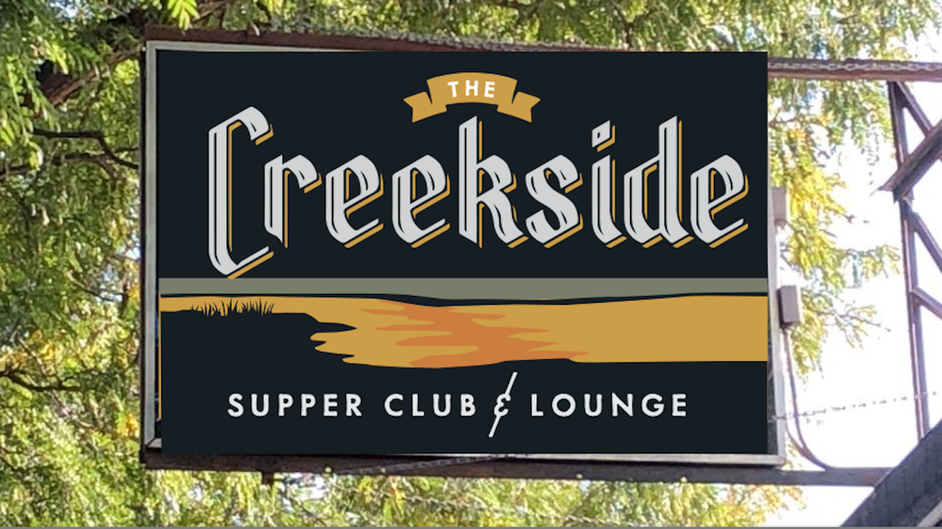 A sign with Creekside Supper Club in white letters above orange