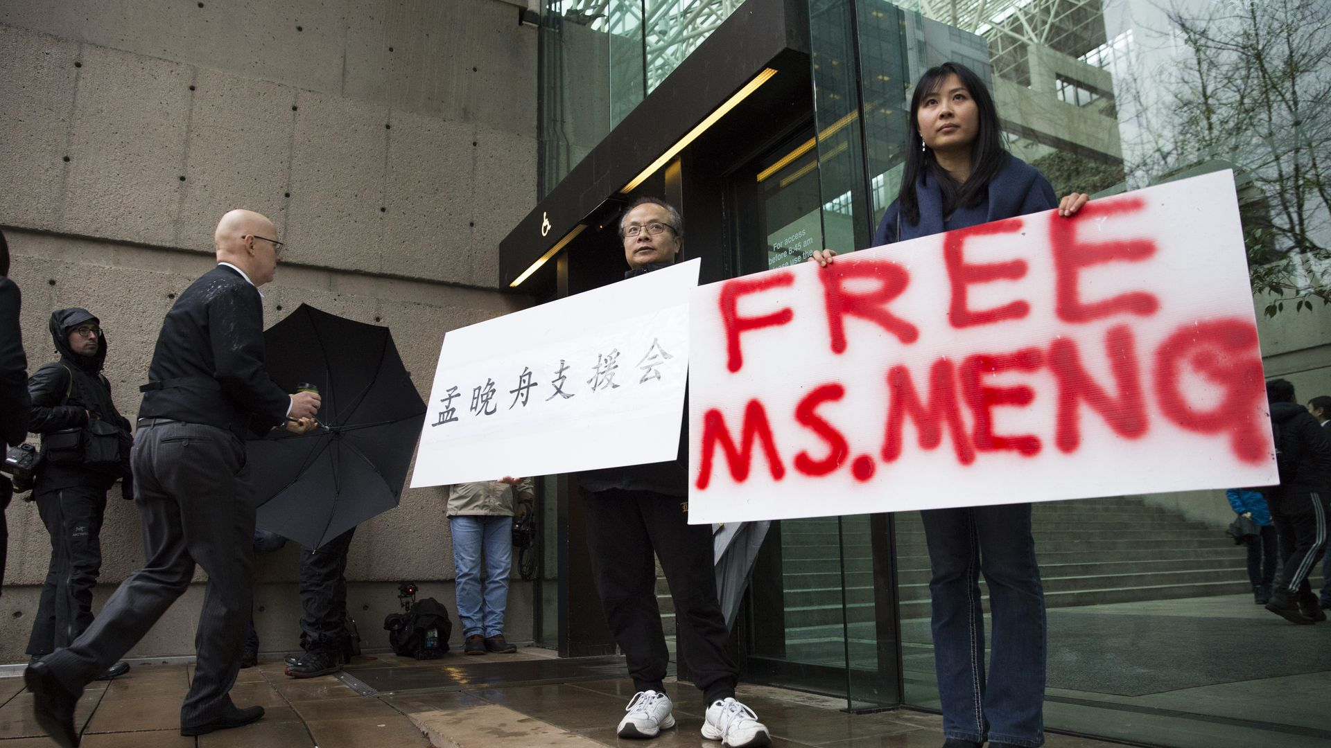 Protesters holding Free Meng signs.