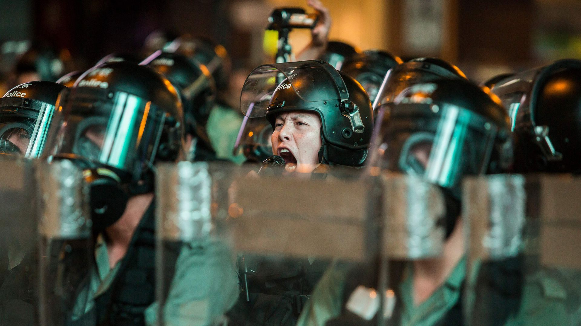 This image shows a riot officer yelling with his face exposed in a line of helmeted officers.