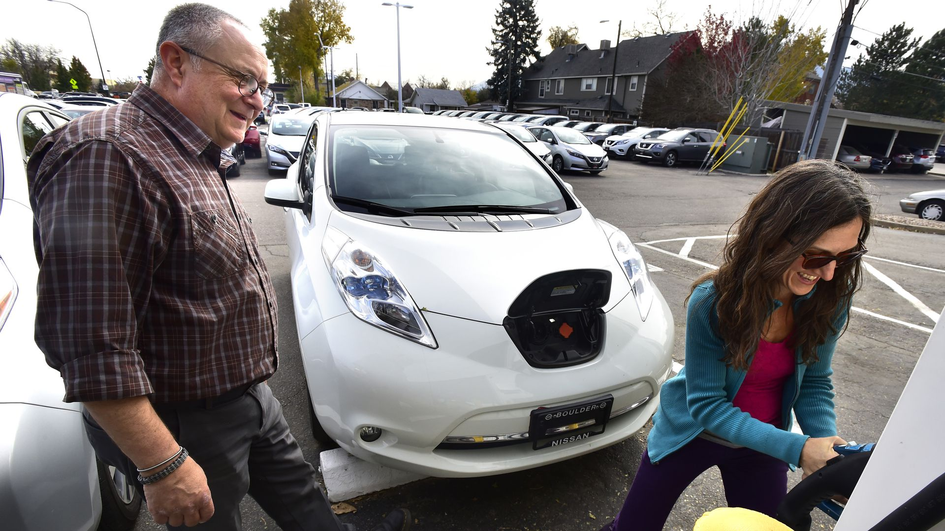 Shanna Solla laughs as she learns how to use the electric charging station with her new Nissan Leaf.