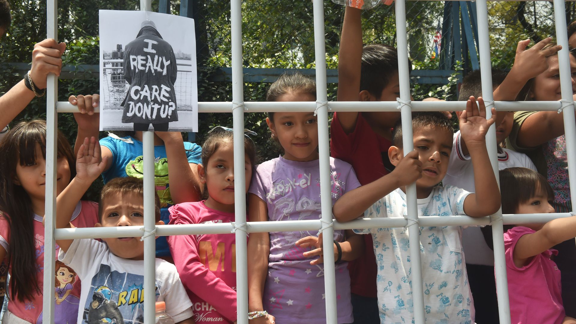 children protesting family separation by standing behind fake jail bars