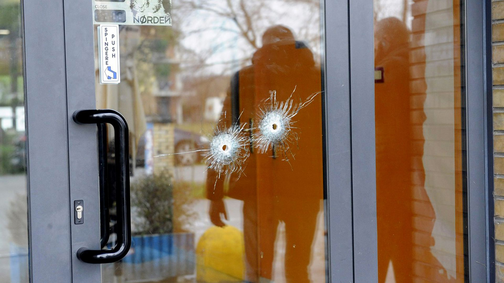 Bullet holes are seen in a glass door following a drive-by shooting at Macerata.