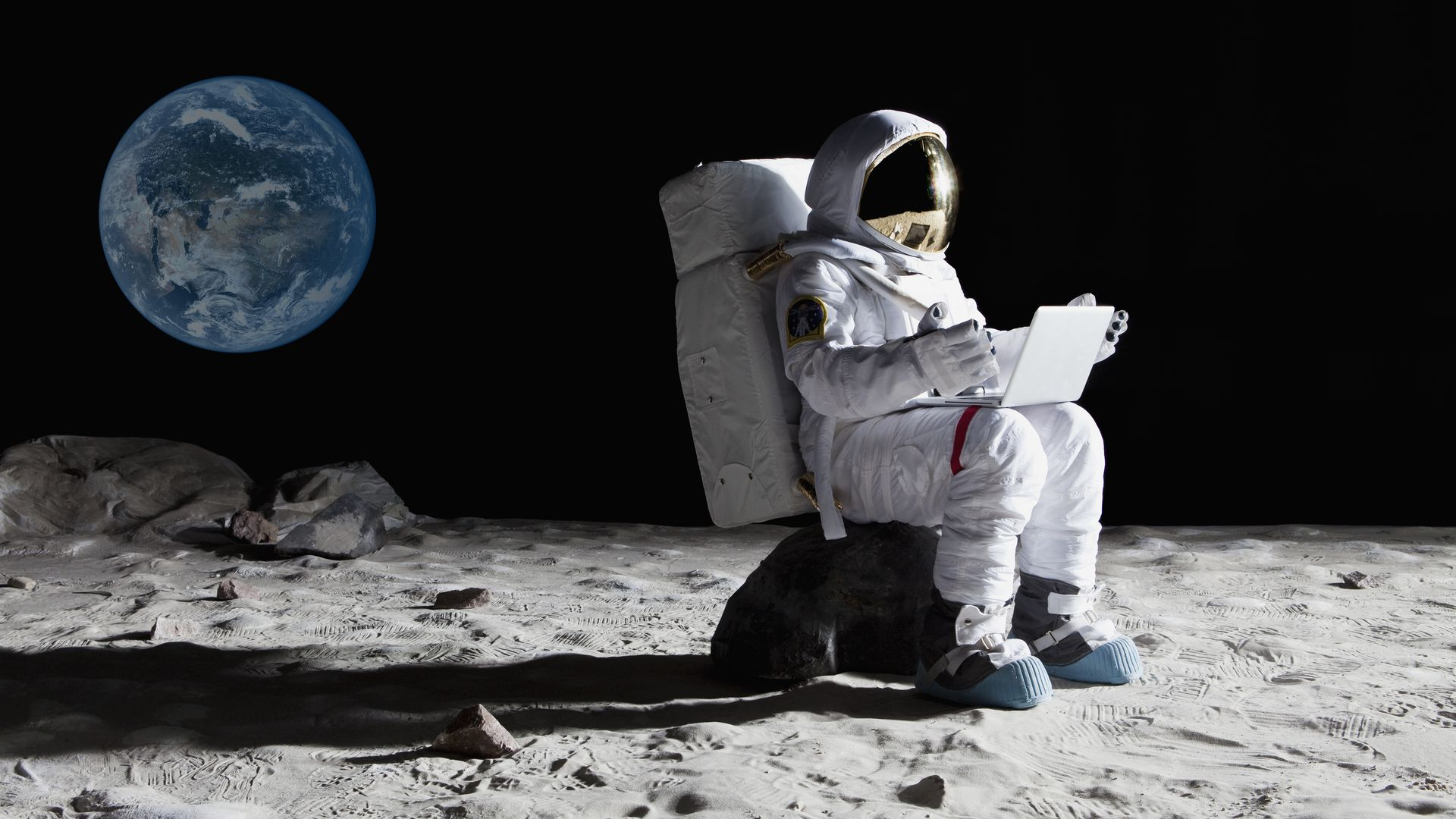 Man uses laptop on the moon.