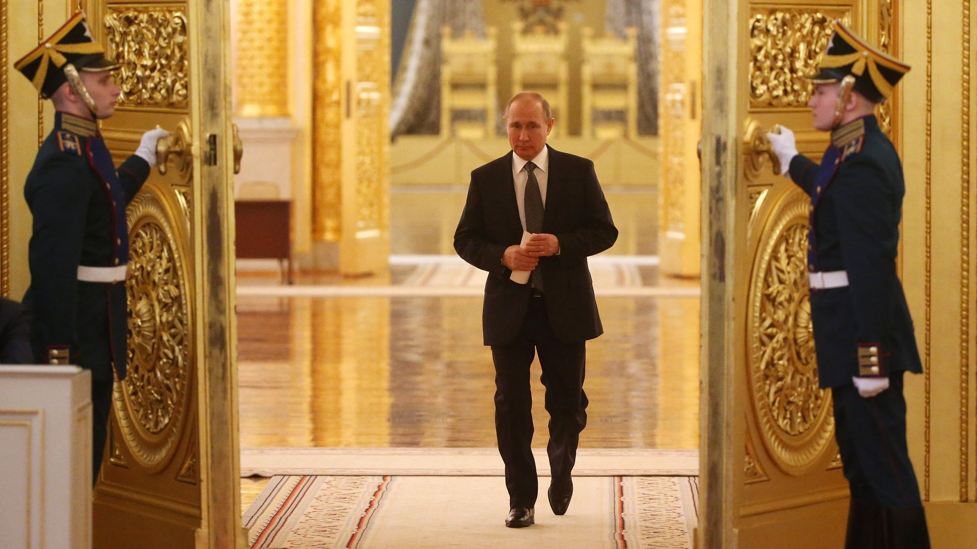 Vladimir Putin walks through golden doors at the Grand Kremlin Palace.