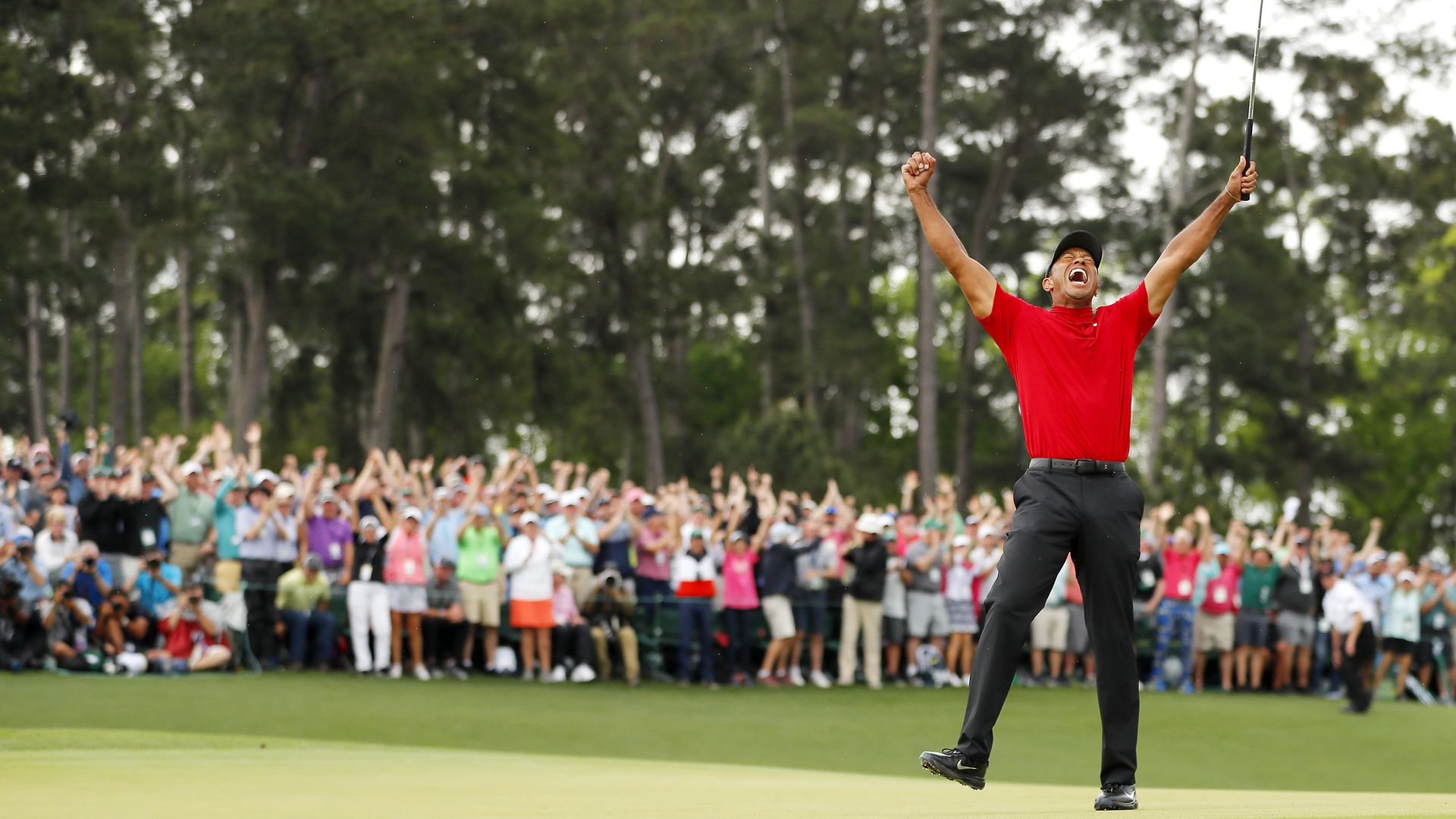 Tiger Woods celebrates on the green