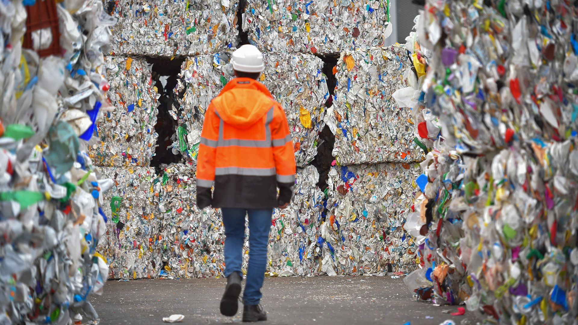 An employee walks through plastic wastes waiting to be recycled at a sorting center in France
