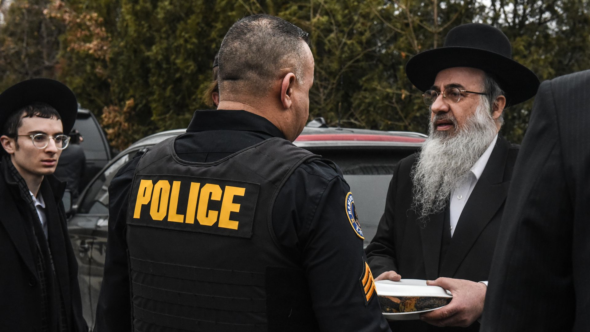 A Ramapo police officer stands guard in front of the house of a rabbi