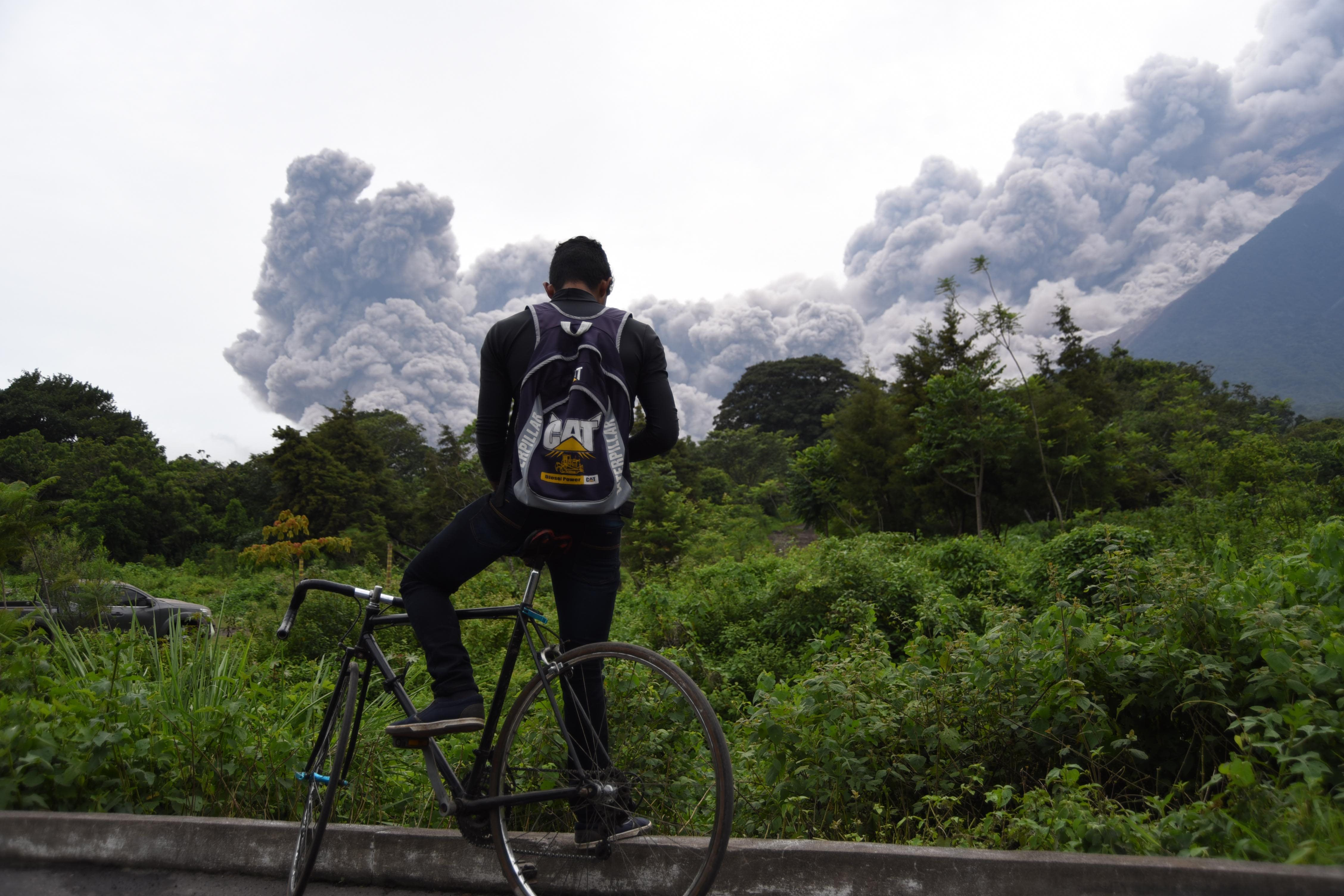 A man looks at the Fuego Volcano in eruption