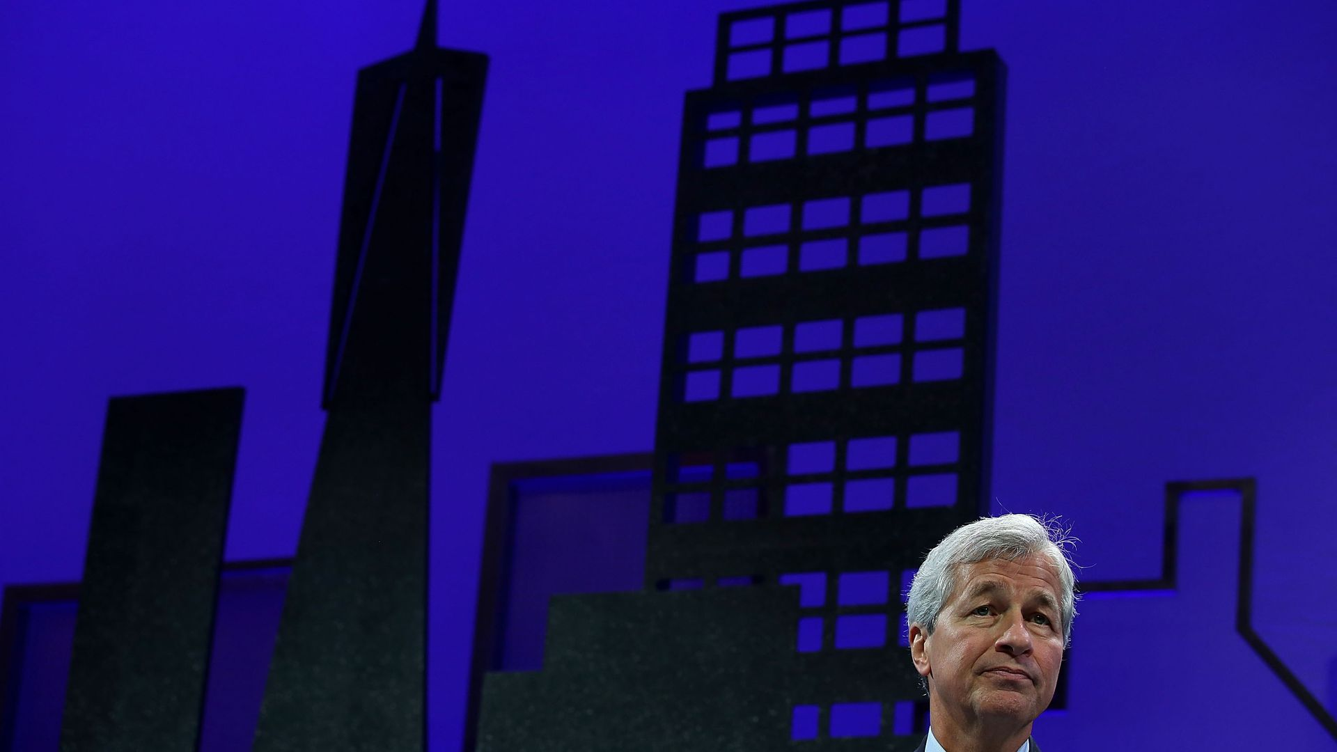 A photo of JPMorgan CEO Jamie Dimon with a cityscape in the background.