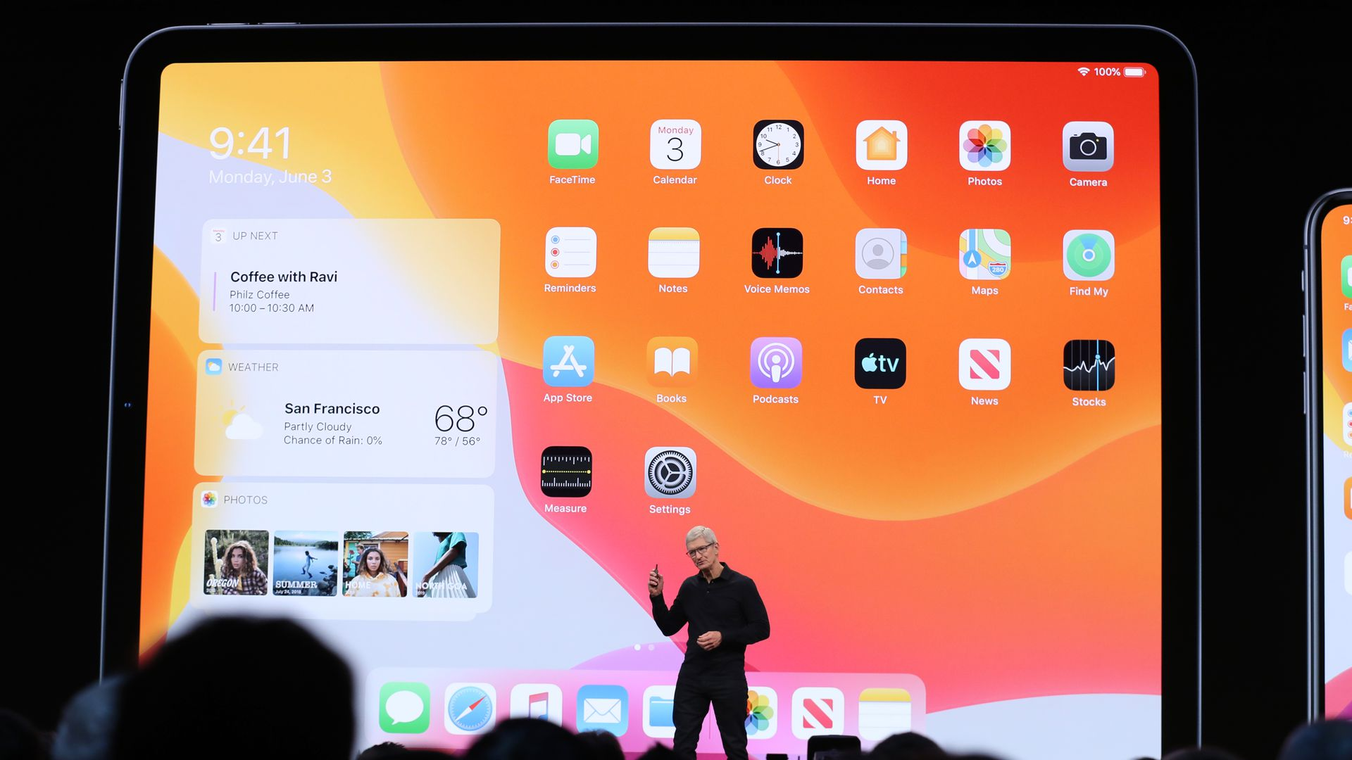 In this image, Tim Cook stands in front of a giant screen shot of an Apple product.