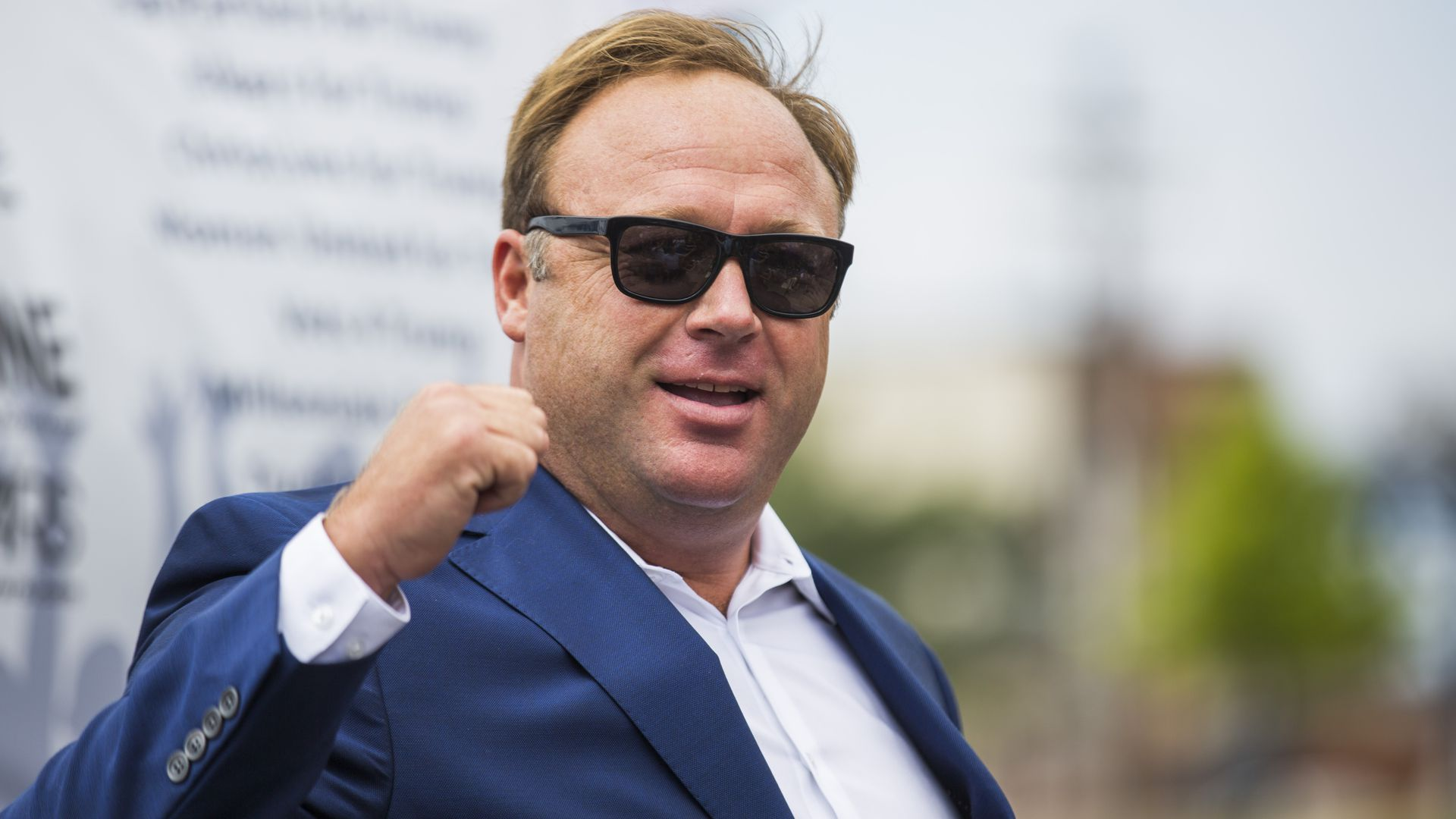 Alex Jones wearing a blue suit and sun glasses.
