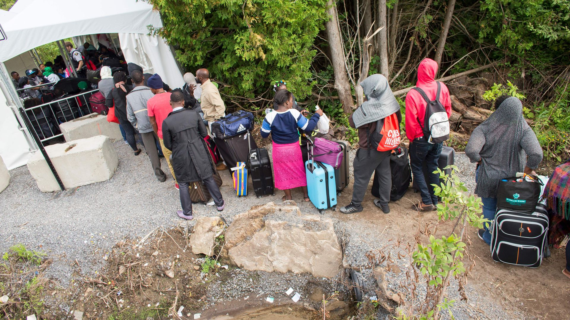A long line of asylum seekers wait to illegally cross the Canada/US border near Champlain, New York