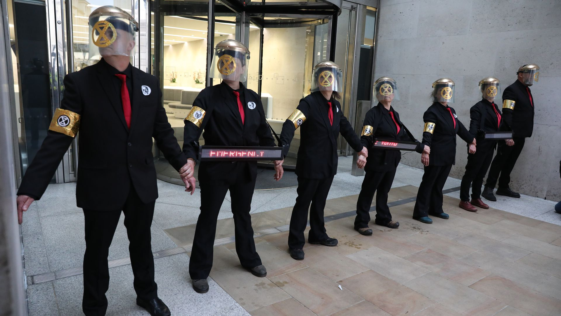 Extinction Rebellion protesters who have glued themselves to the entrances of the London Stock Exchange.
