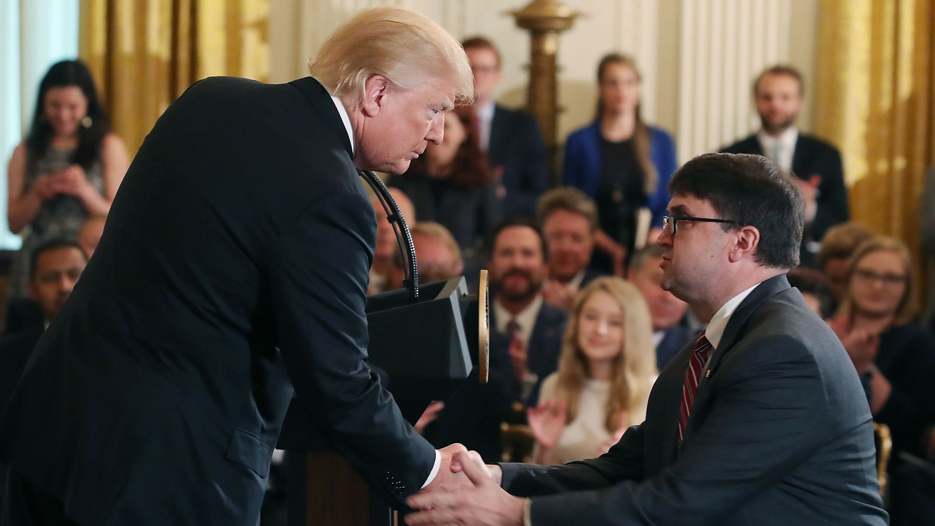 President Donald Trump leans down to shake hands with Robert Wilkie after nominating him to be next Veterans Affairs Secretary, during an event in the East Room at the White House