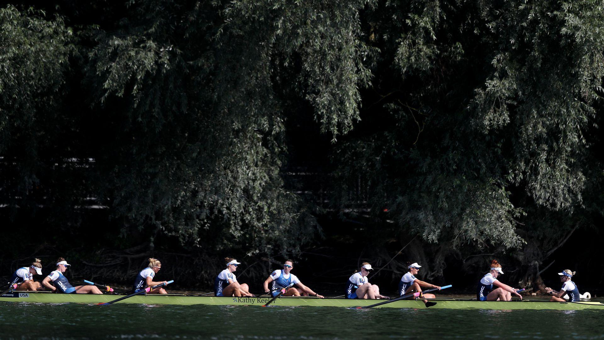 Women rowers sit in a boat.