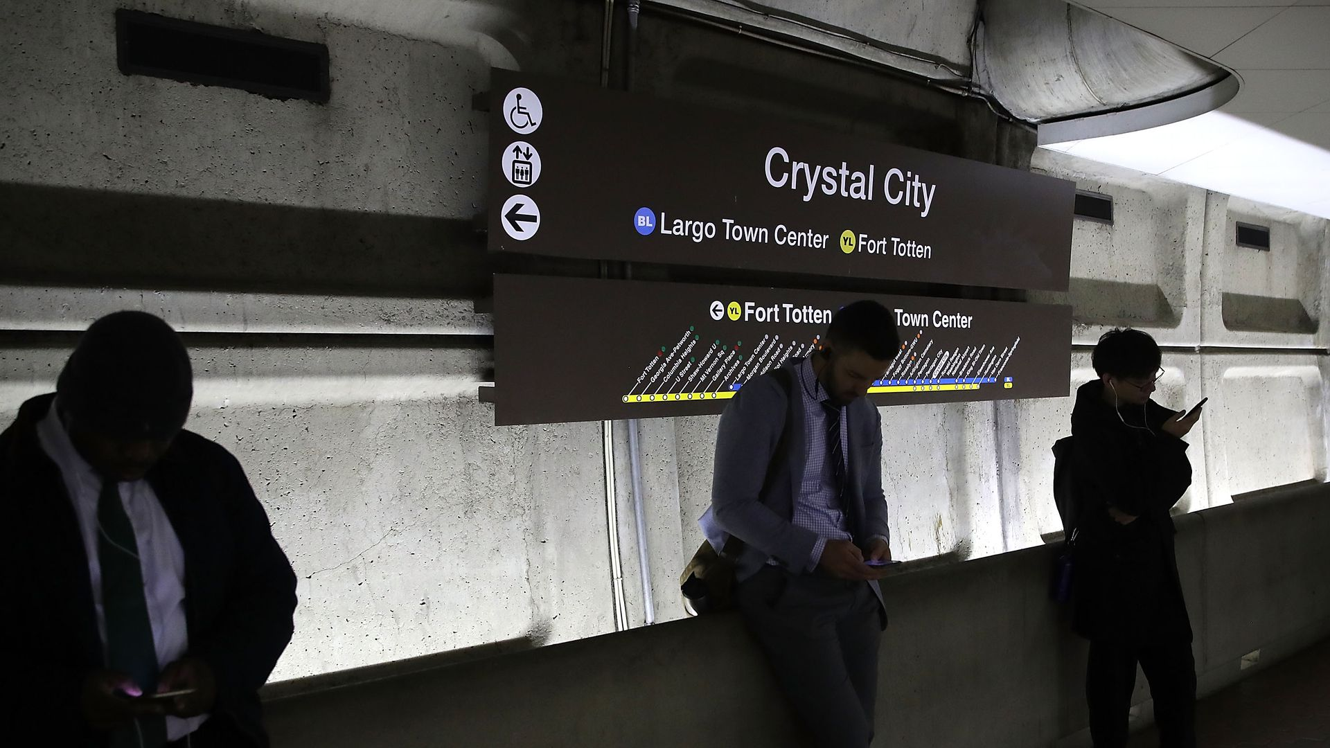 """People wait on a subway platform underneath a sign that says """"Crystal City"""""""