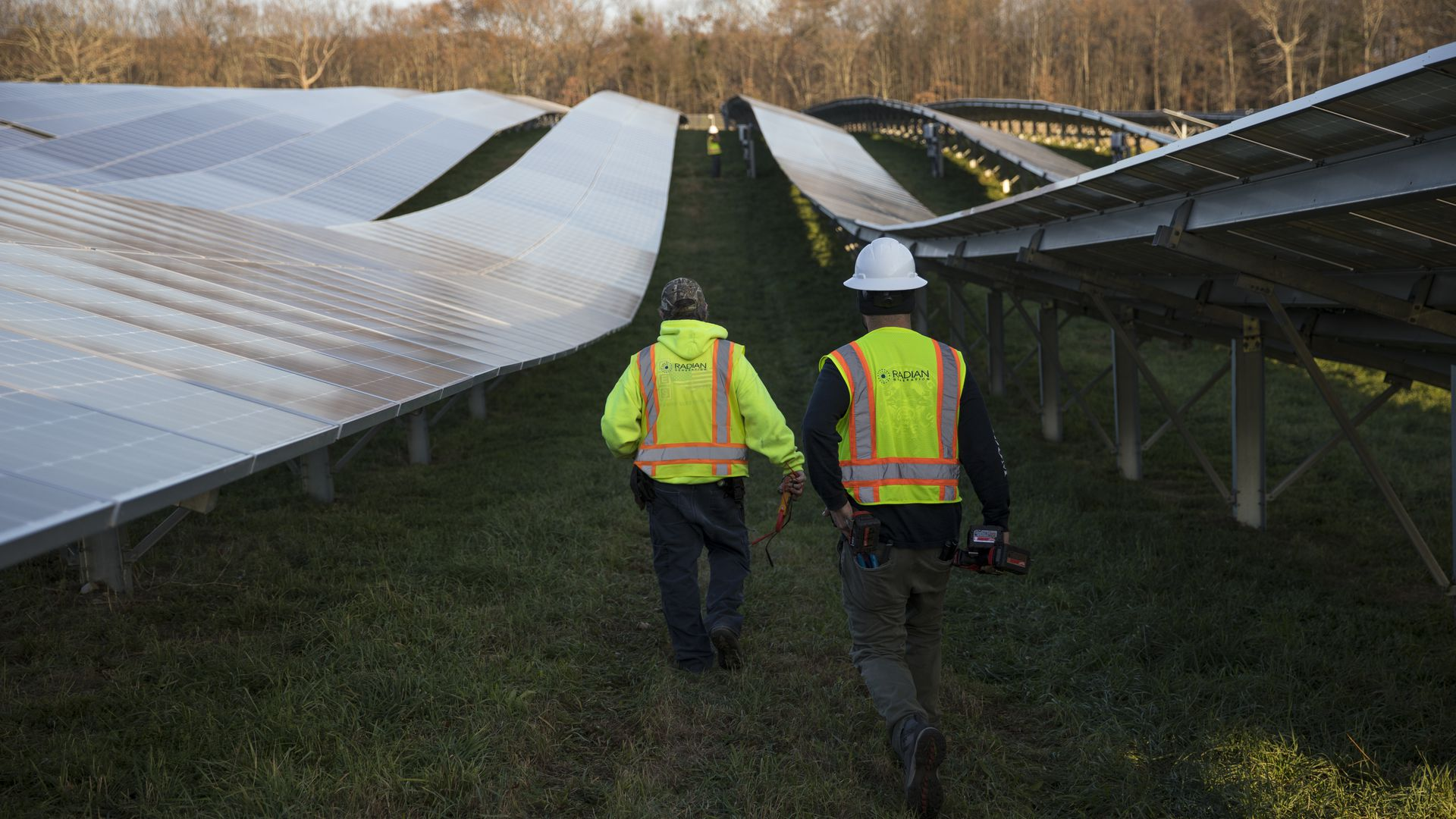 Employees from a Radian Generation's operations and maintenance team change out a faulty solar inverter along a row of solar panels
