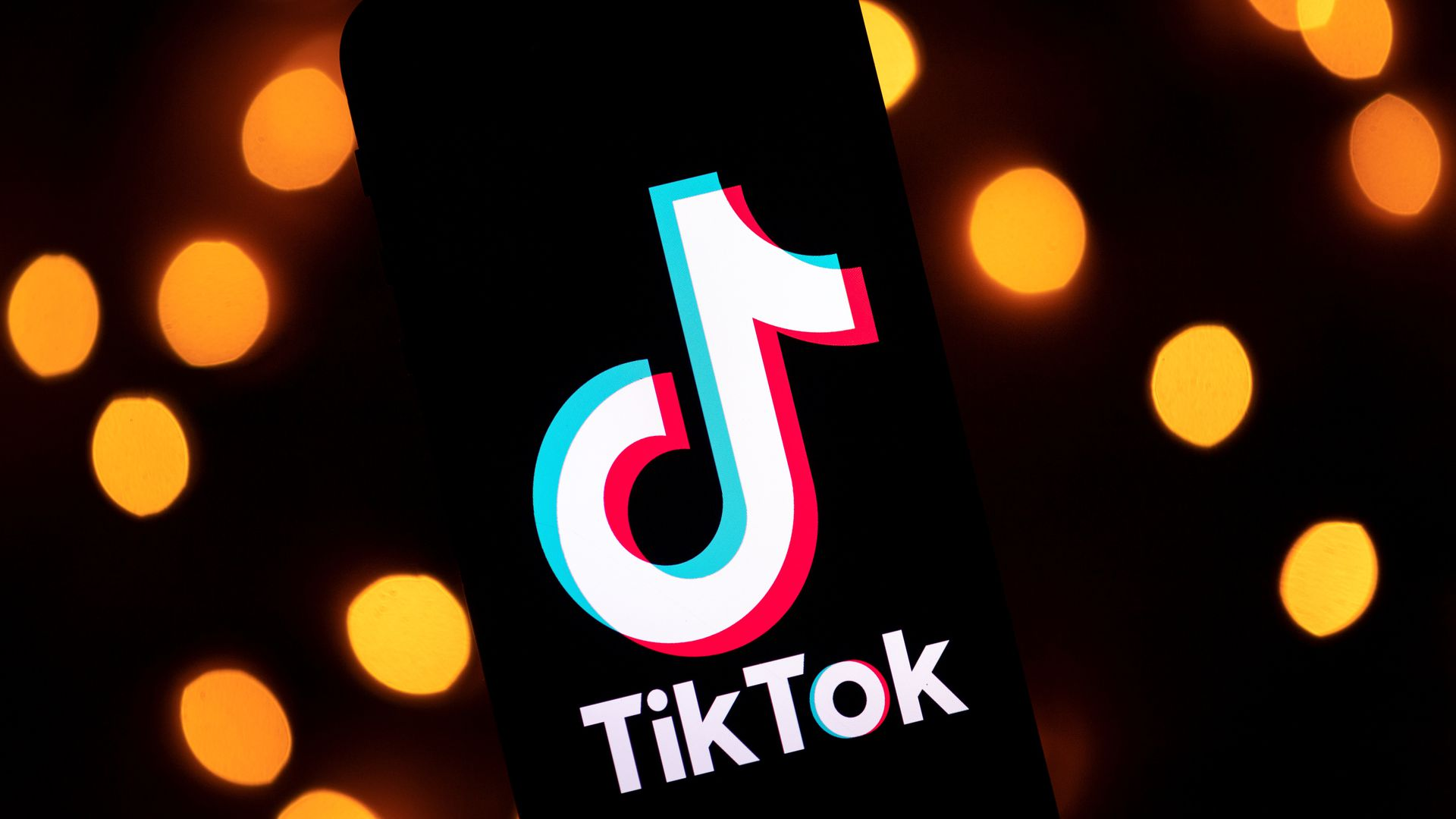 A photo of TikTok's logo with lights behind it.