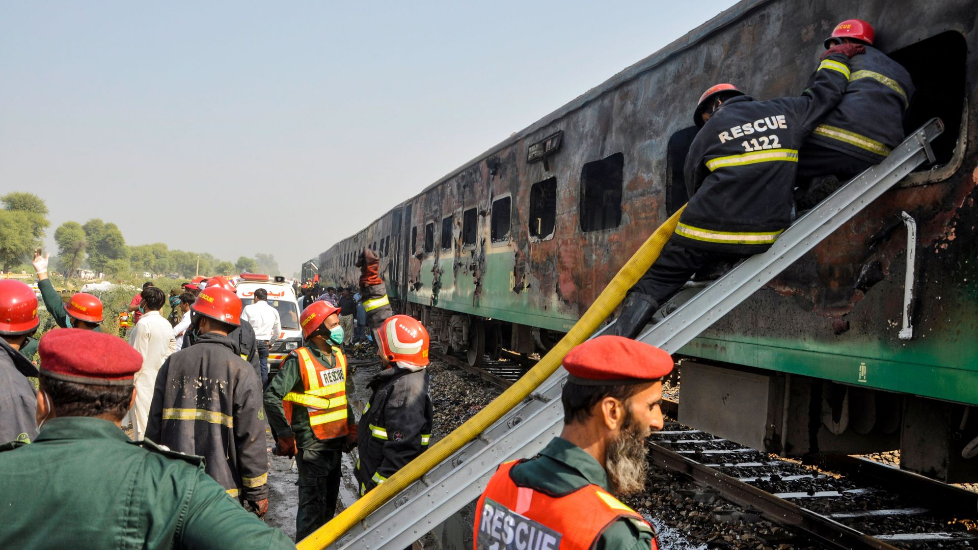 Firefighters work to cool down the burnt-out train carriages.