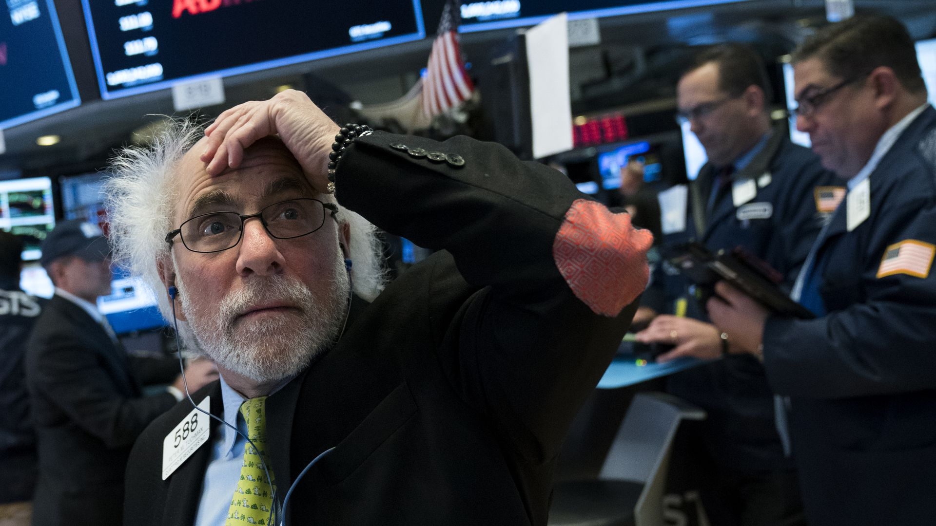 A photo of a trader on the floor of the New York Stock Exchange looking shocked.