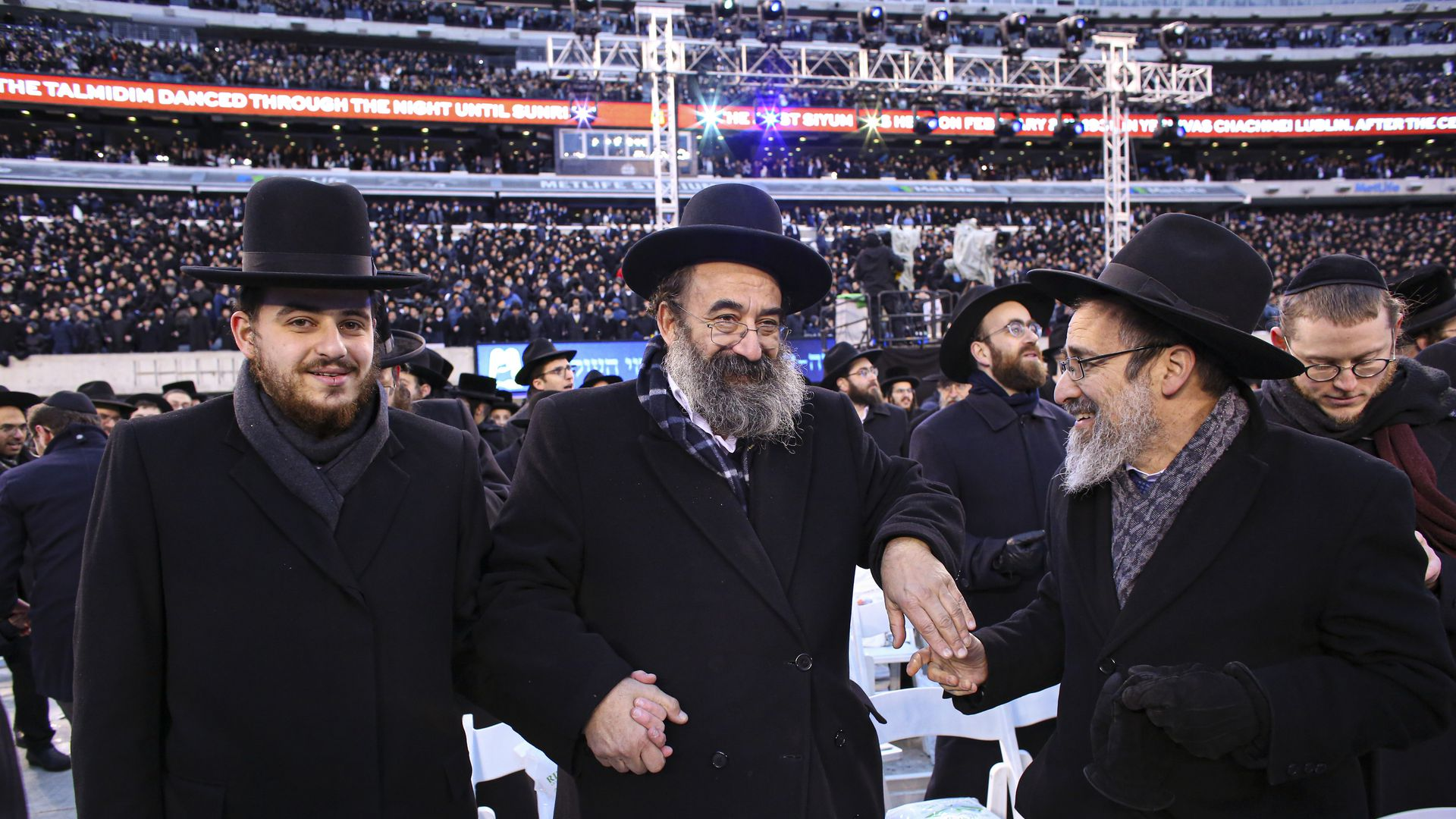 Men dance as they gather with others in MetLife Stadium on January 1, 2020, in East Rutherford, New Jersey