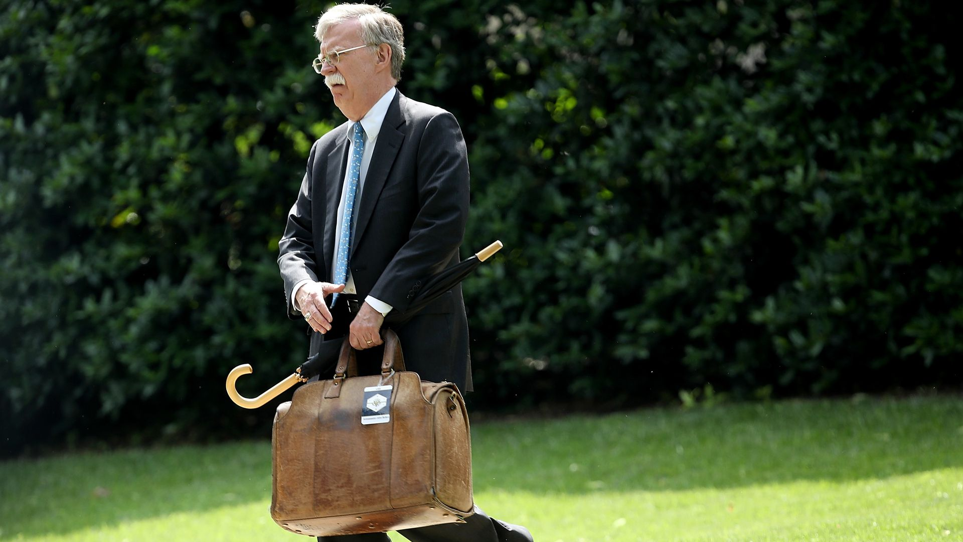 John Bolton carrying luggage and umbrella