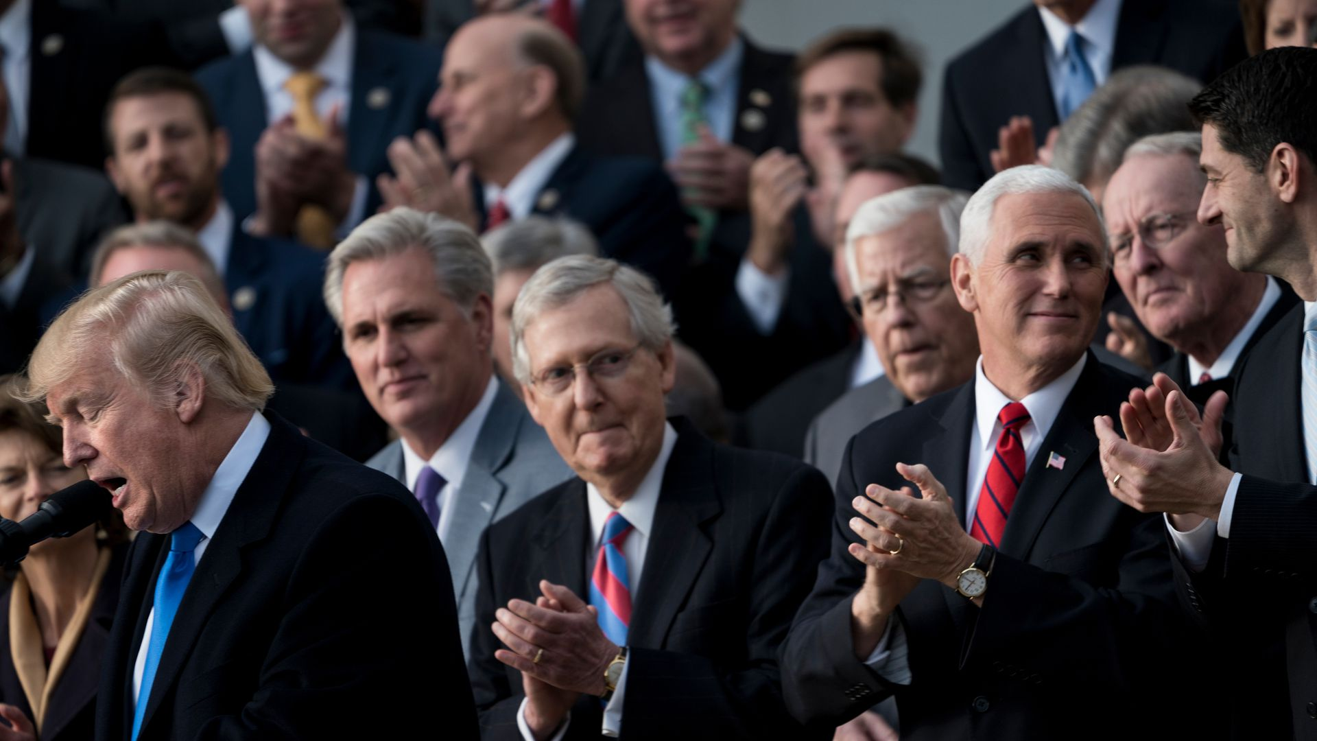 Republican male leaders clapping after passing tax cuts