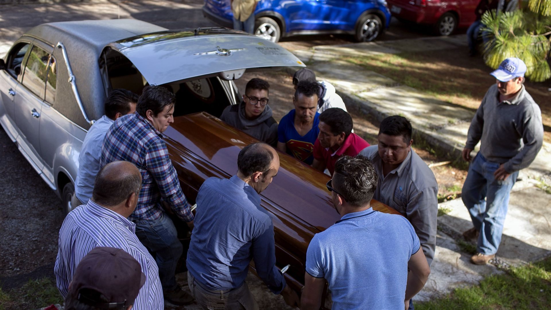 Coffin is pulled out of car trunk by group of people