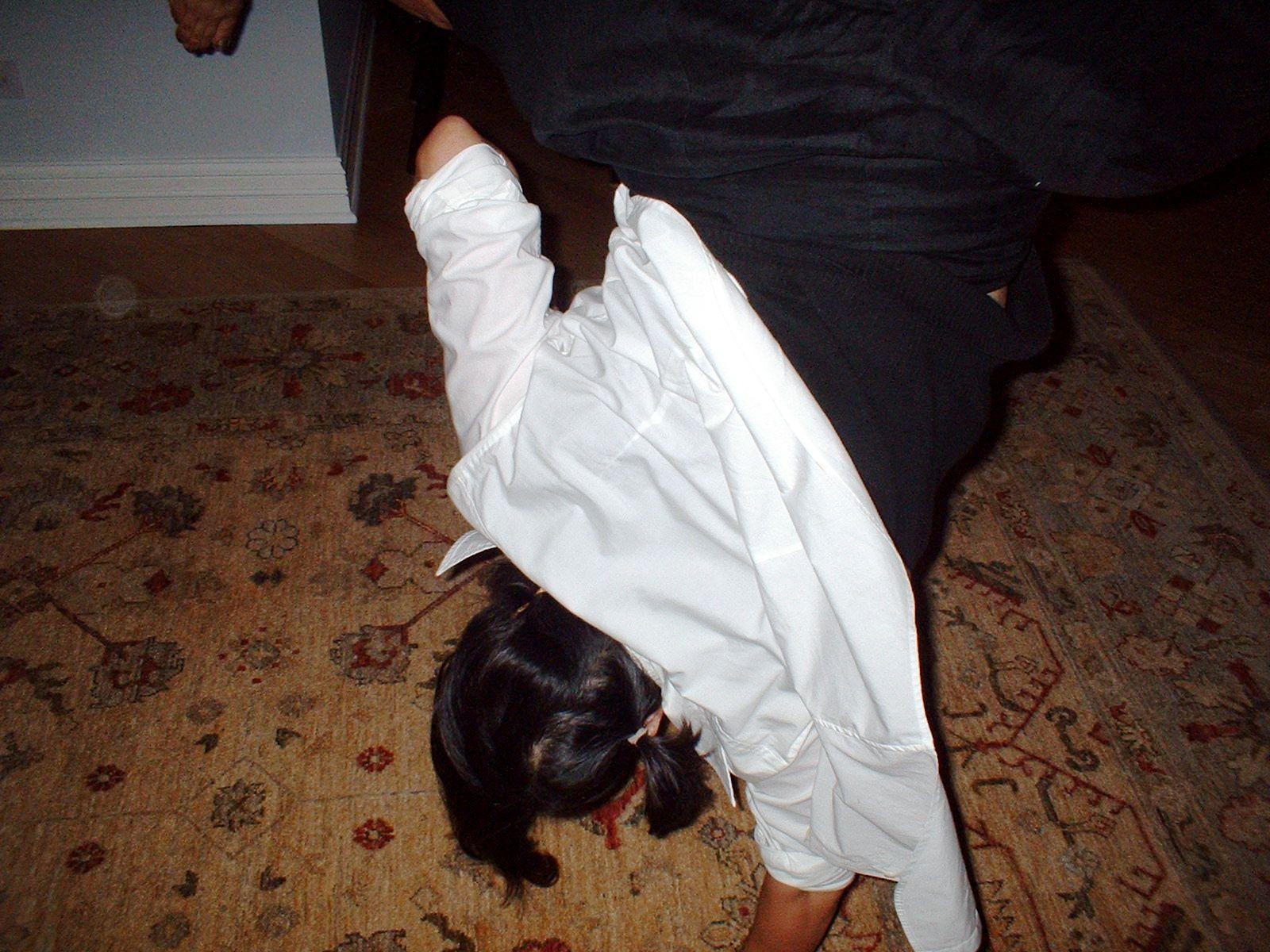 Girl upside down doing cartwheel.