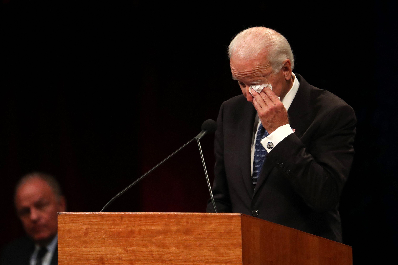 Joe Biden uses tissue to wipe eyes.