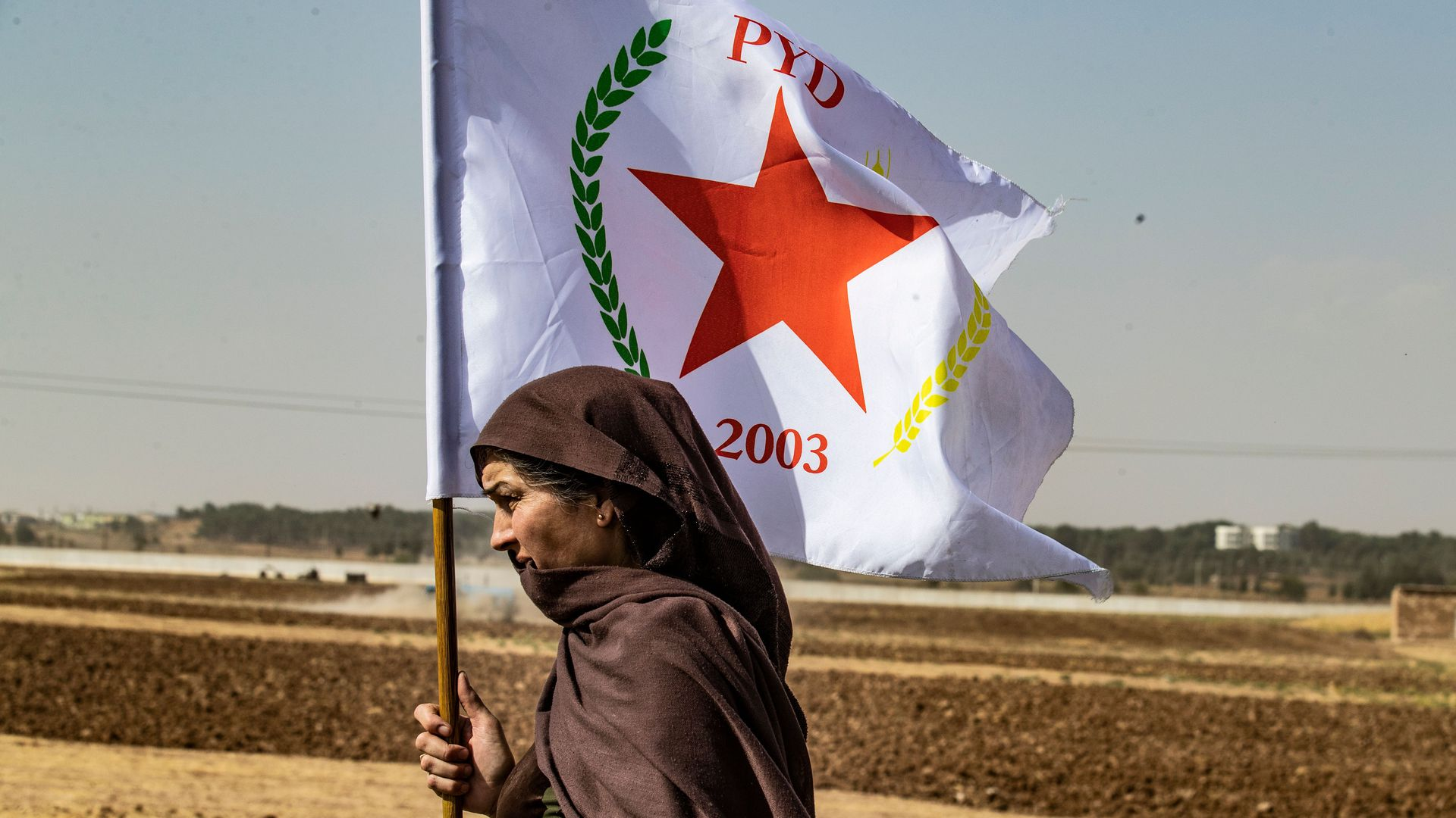 A Syrian Kurdish woman waves the flag of the Democratic Union Party during a demonstration against Turkish threats in Syria near the Turkish border.