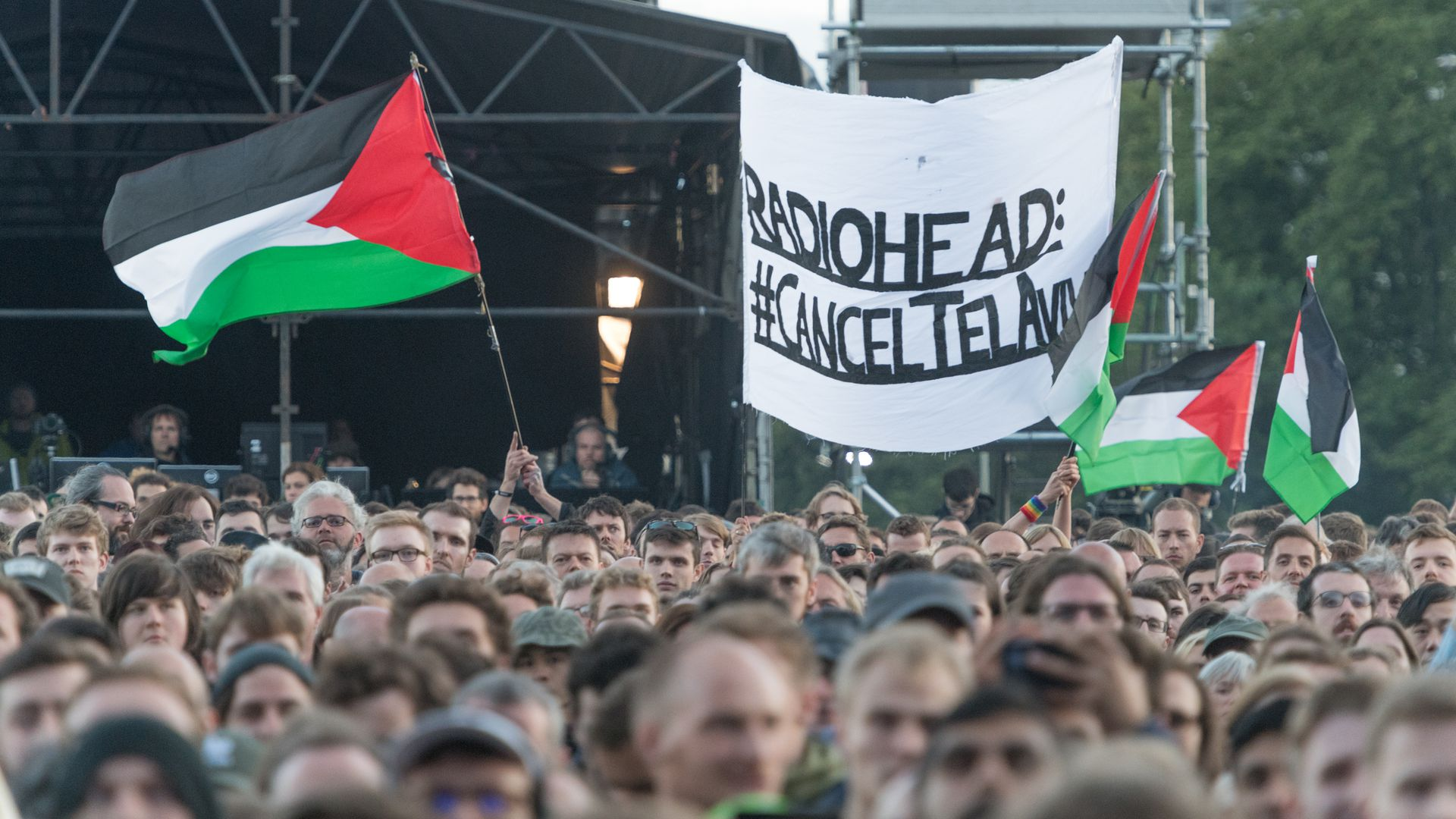 Protestors hold up a banner calling for Radiohead to cancel a show in Israel.