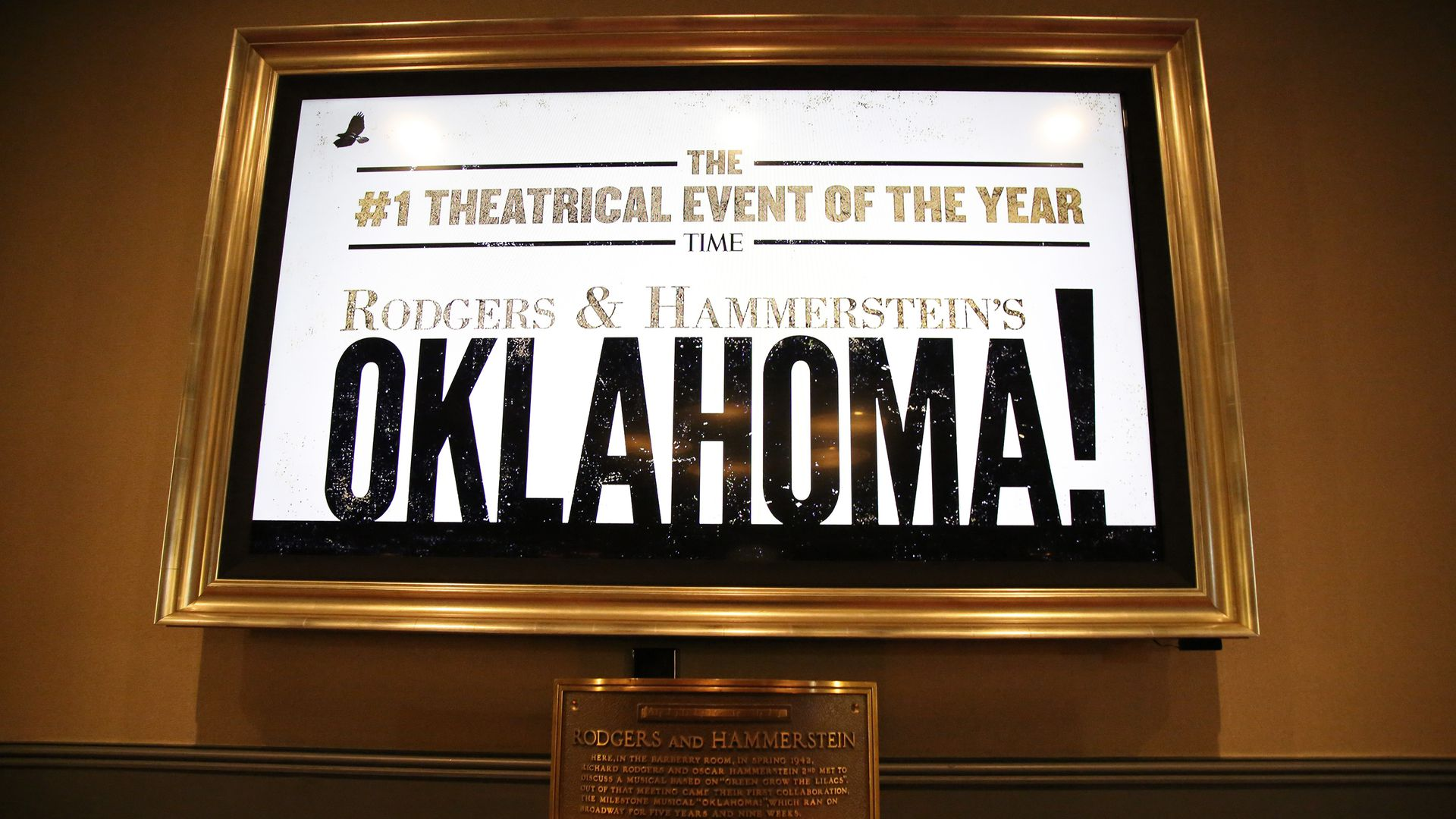 A plaque that reads Rodgers & Hammerstein rests under a display advertising for the Oklahoma! show