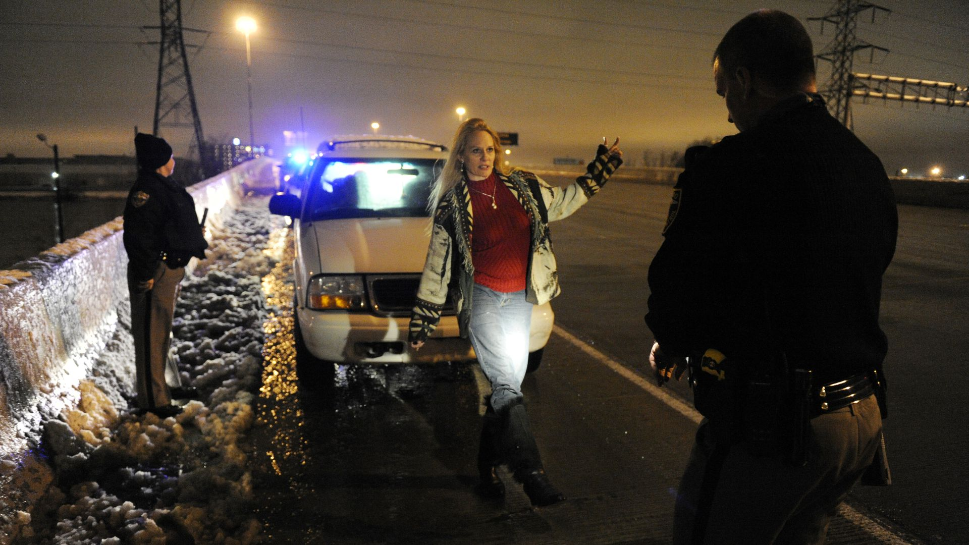 Woman performs sobriety test in front of a copy in the dark on the side of a highway