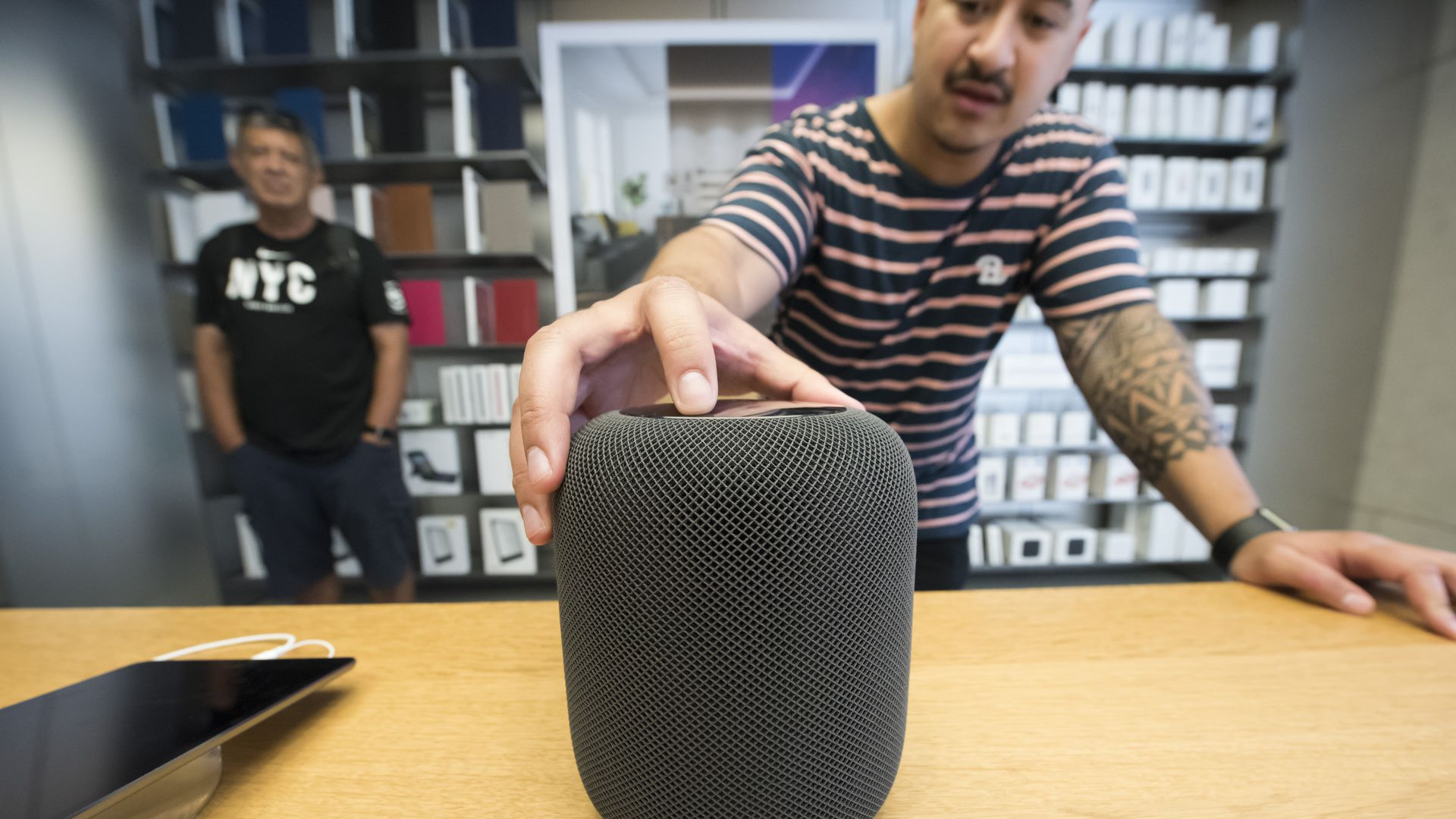 Apple HomePod smart speaker on a table while a man is palming it.