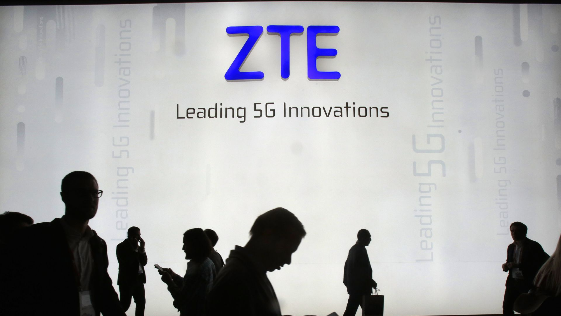 ZTE logo on wall with shadowy human figures below