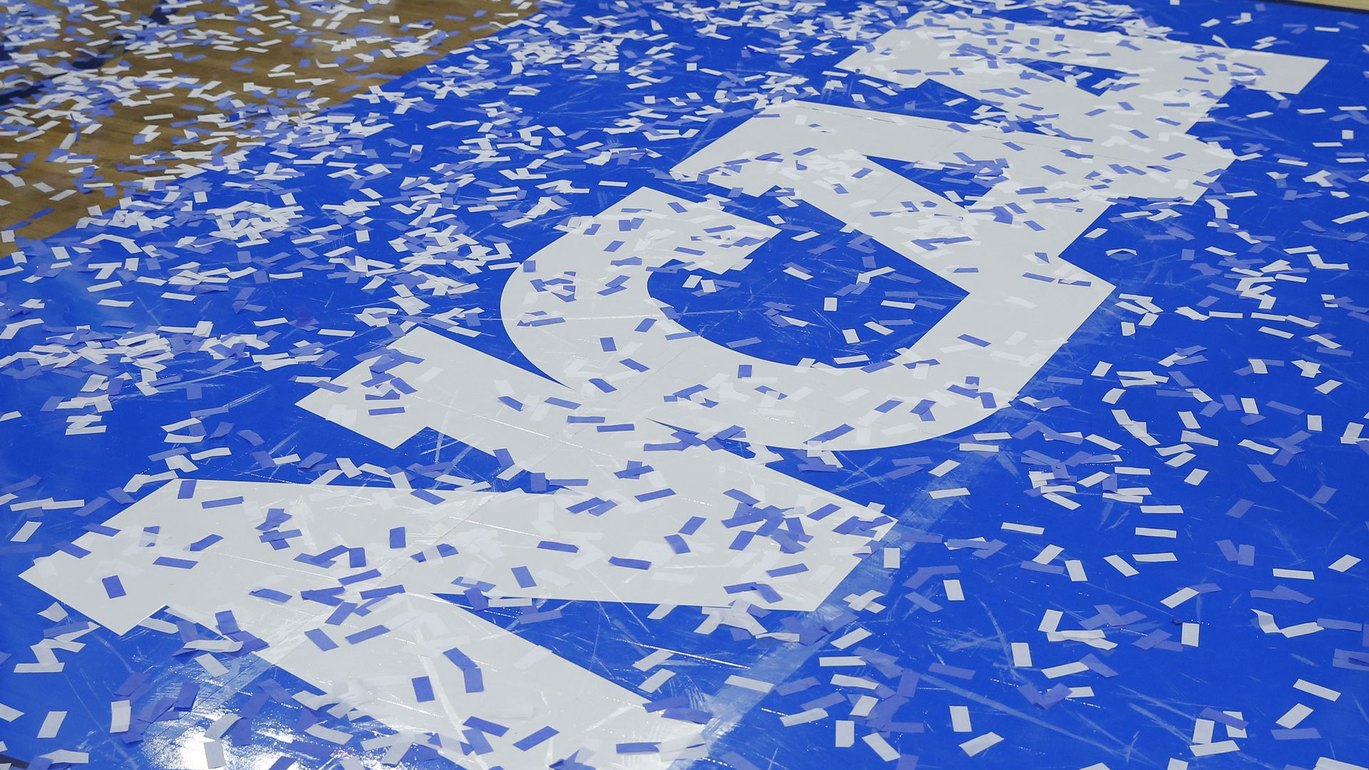 In this image, the blue and white block letter logo for NCAA is on the floor of a basketball court as confetti falls onto the floor.