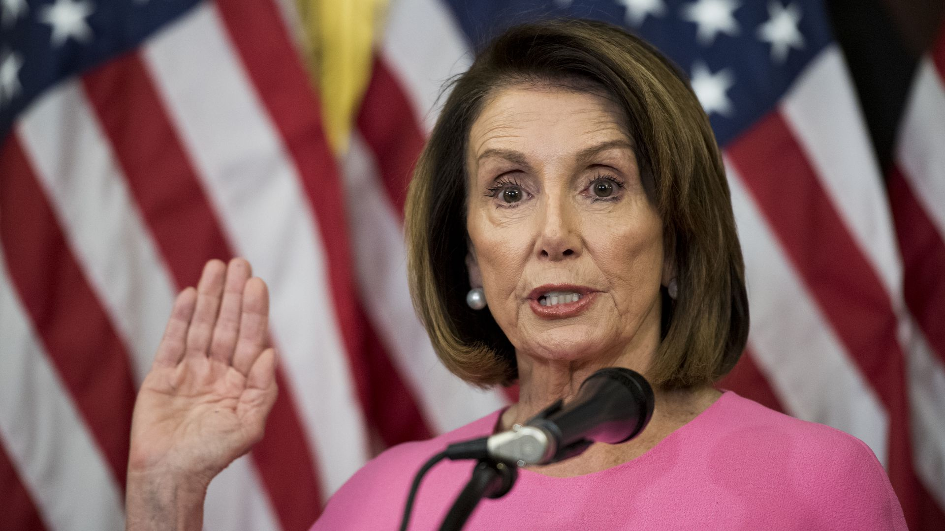 Nancy Pelosi raises her hand as if she's taking the oath of office