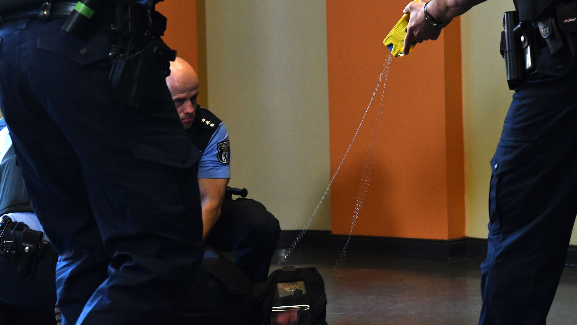 A police officer demonstrates how to use a Taser.
