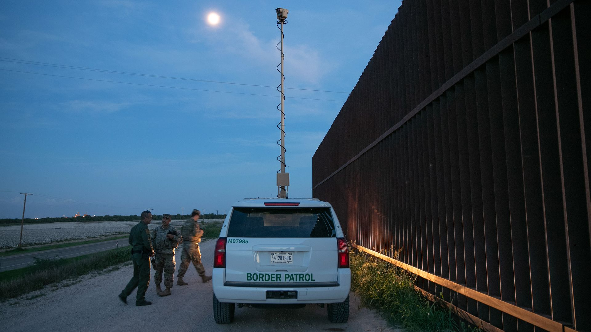 Border patrol car parked by a border fence at dusk.