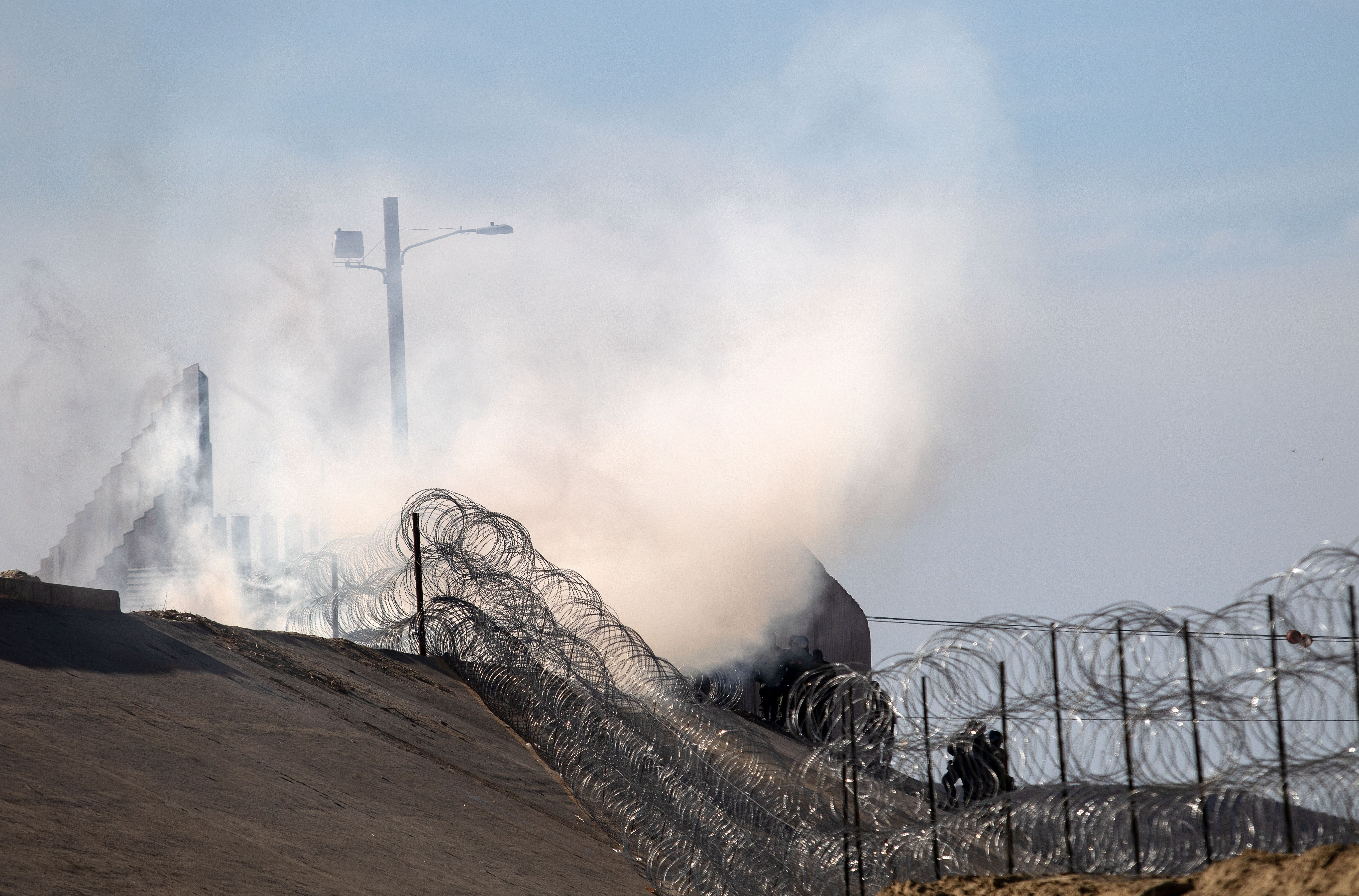 Gas rising over a border fence covered in barbed wire