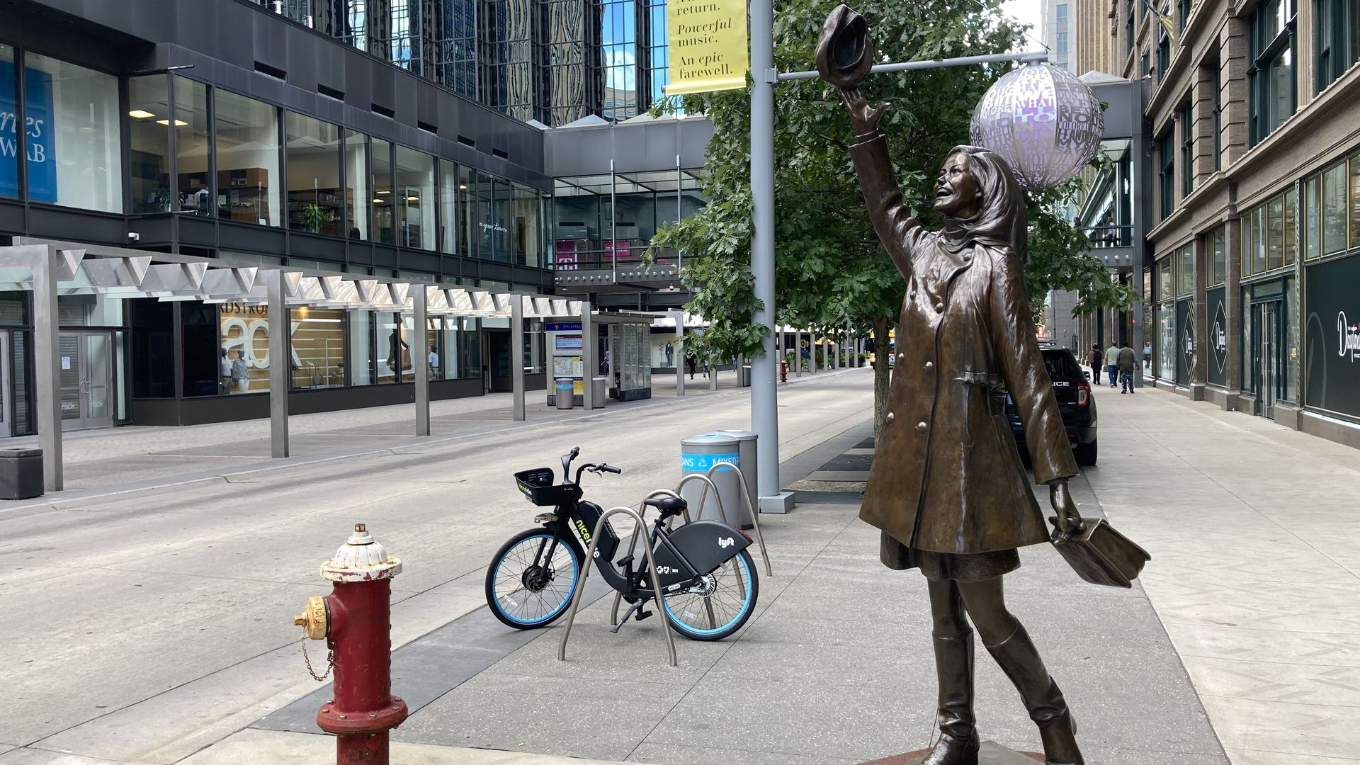 Mary Tyler moore statue, with downtown in the background. Nicollet mall is empty
