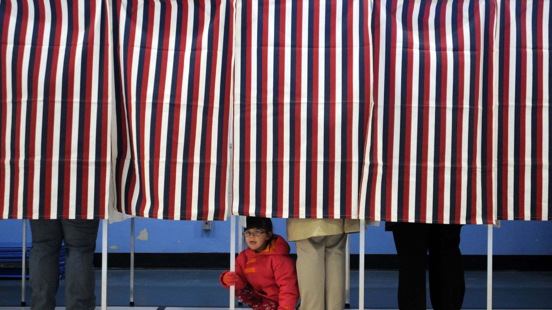 Poll booths with red, white, and blue curtains, while people vote.